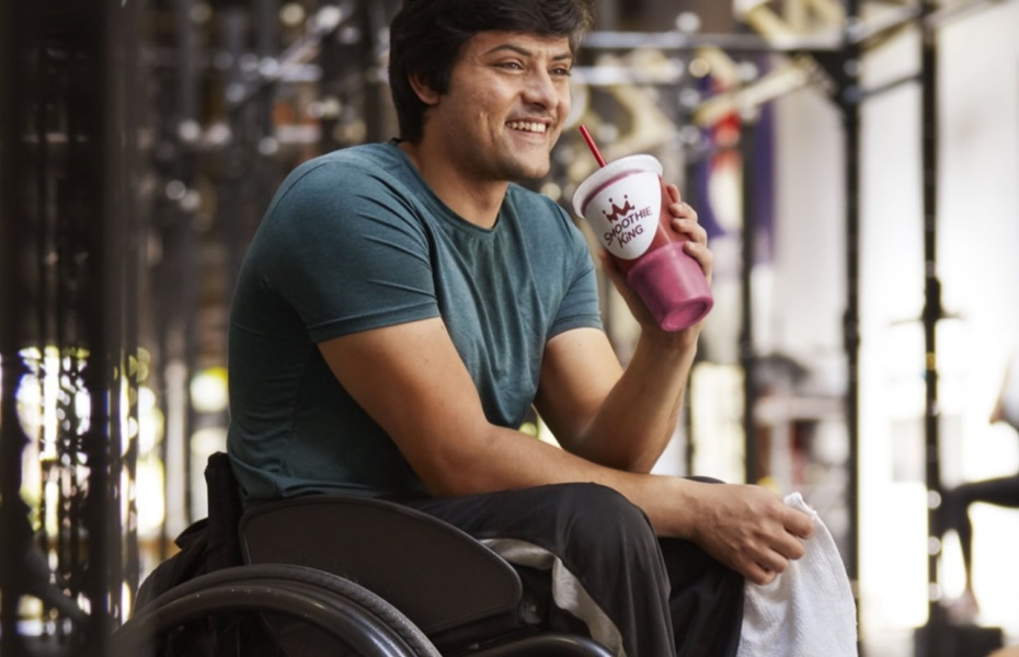 Athlete holding a smoothie in a wheelchair