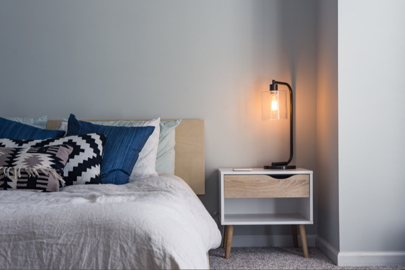 Made bed with end table and ignited lamp