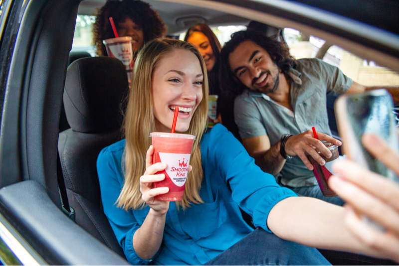 Friends taking a selfie in a car with their Smoothie King drinks