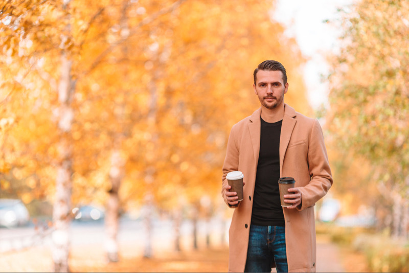 Man holding coffees with fall trees in the background