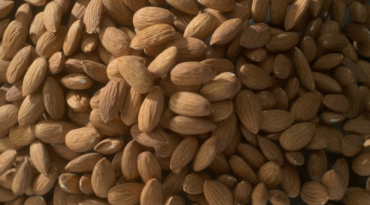 a close-up image of a pile of overflowing almonds